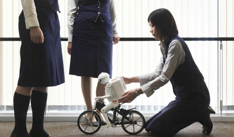 Fotografía de Mujer japonesa empujando a un robot en bicicleta