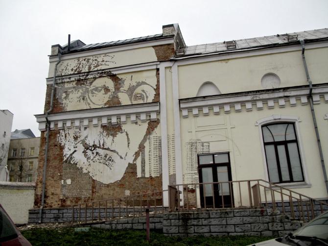 arte callejero esculpiendo en la pared, anciana con gafas