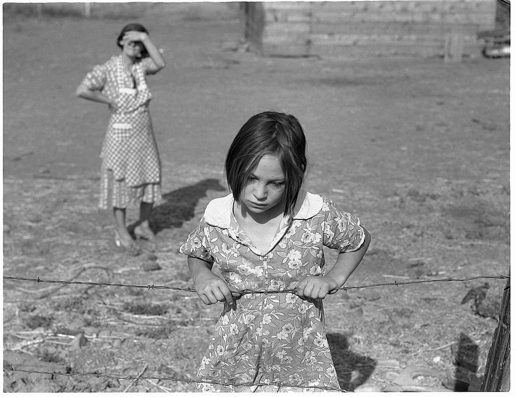 Niña detrás una alambrada, fotografiada por Dorothea Lange