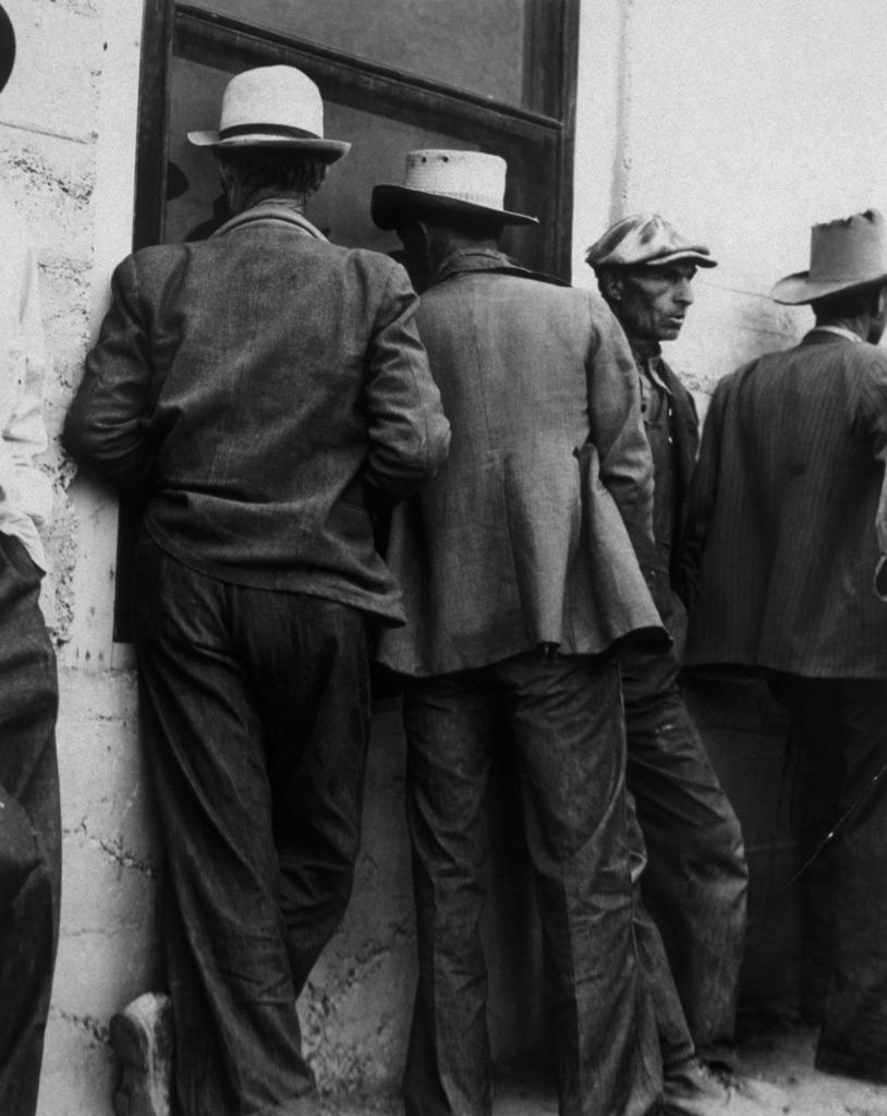 Fotografia en blanco y negro de Hombres en los años 60 haciendo cola