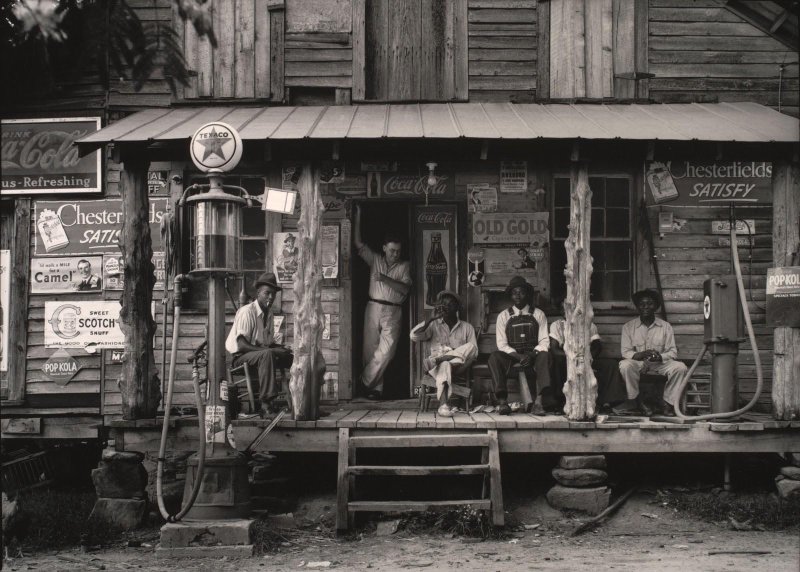 Fotografía de hombres de color en los años 50 en la puerta de una tienda hecha por Dorothea Lange