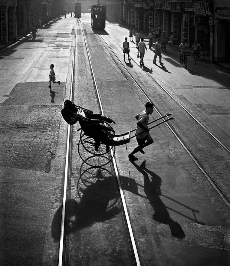 Fotografía en blanco y negro de chico con carrito en una calle de hong kong en el año 1960