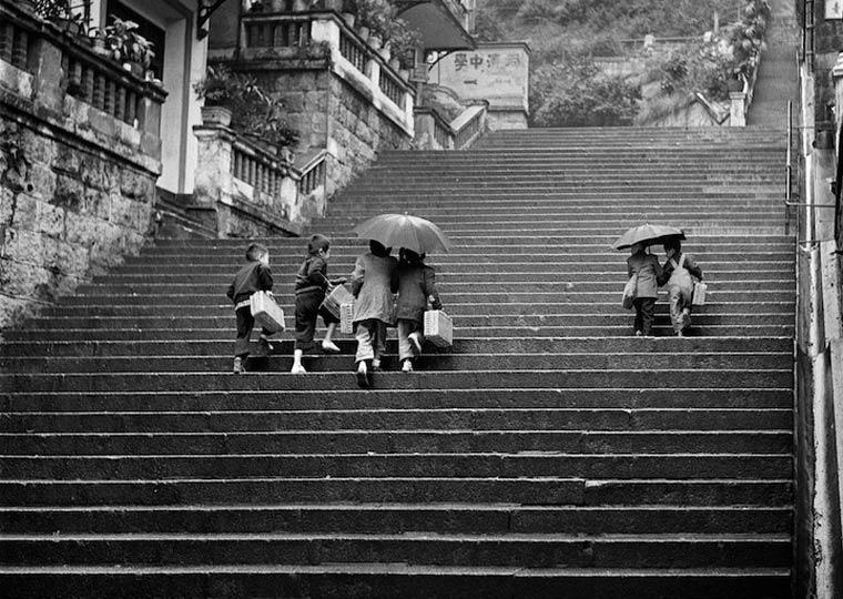 Fotografía en blanco y negro de chicos en una calle de hongkong en el año 1960