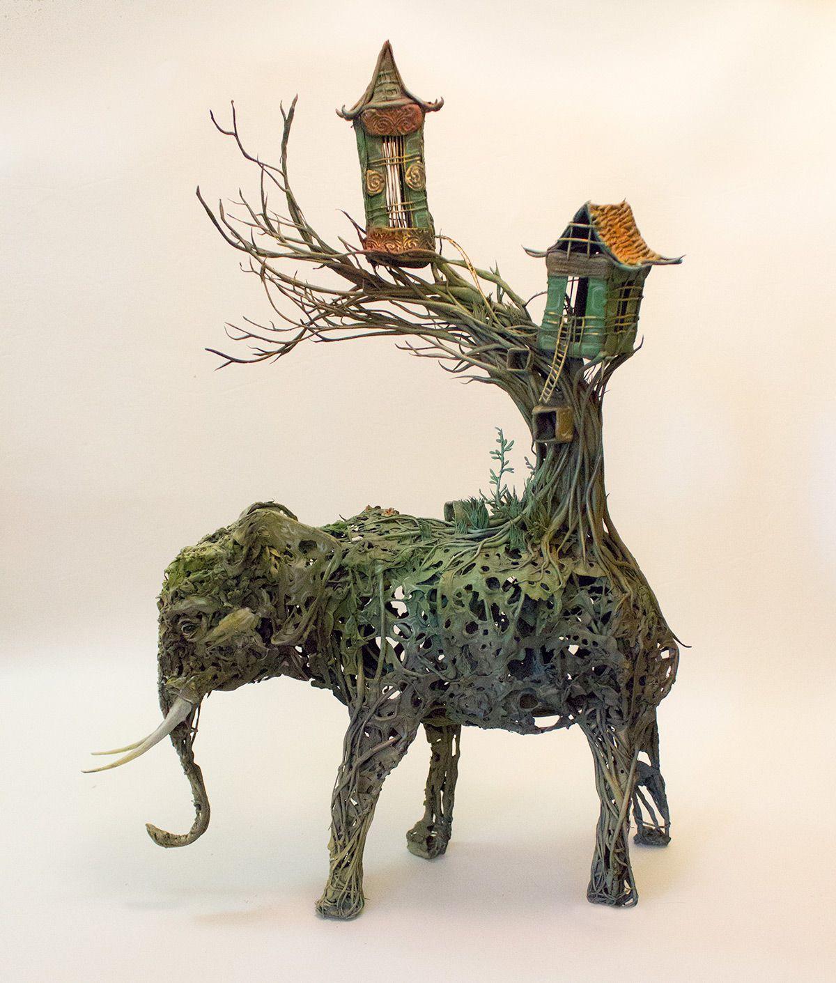 escultura de un elefante con la cola que son unas casa creada con plantas