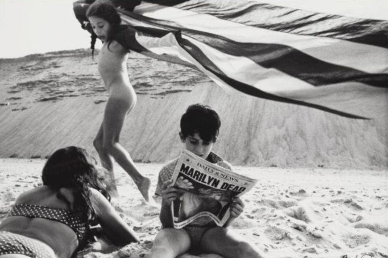 Robert Frank fotografiando a un niño con periódico con la muerte de marilyn monroe