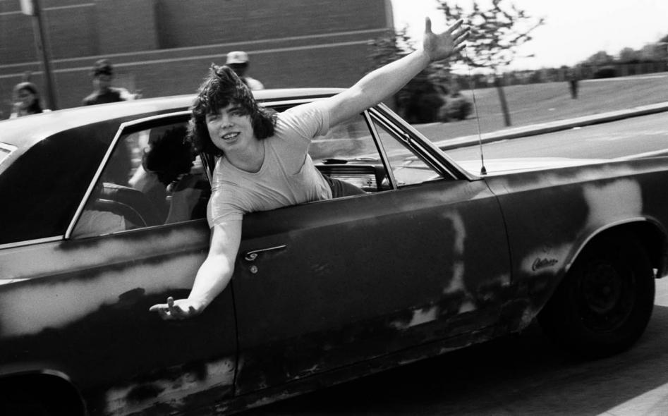 Fotografía de chico saludando desde un coche