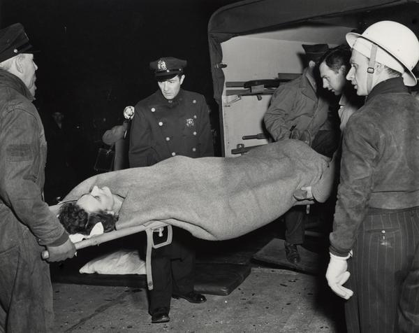 Weegee fotografía a un herido entrando a un ambulancia en 1944.