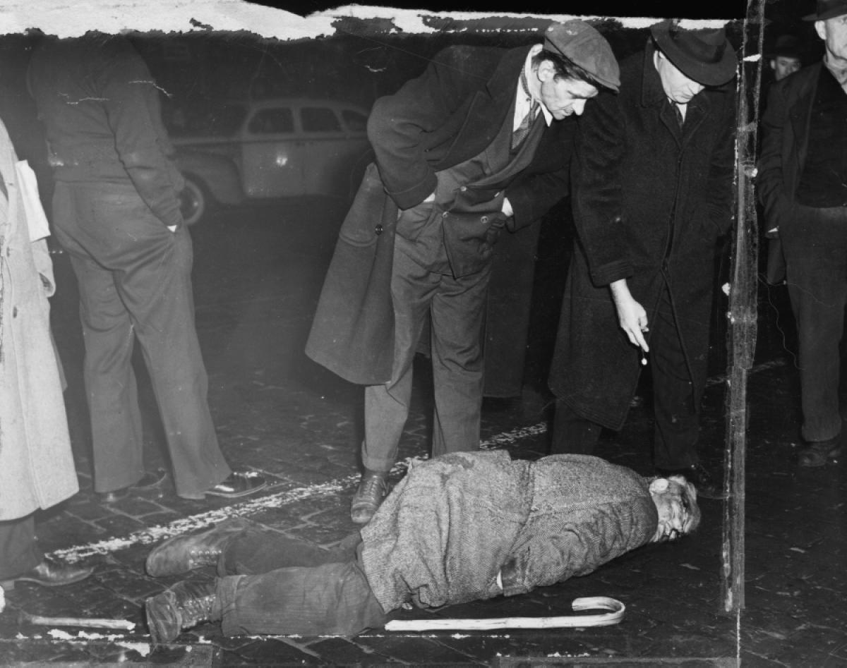 Policía levantando un cadaver en las calles del new york de 1940