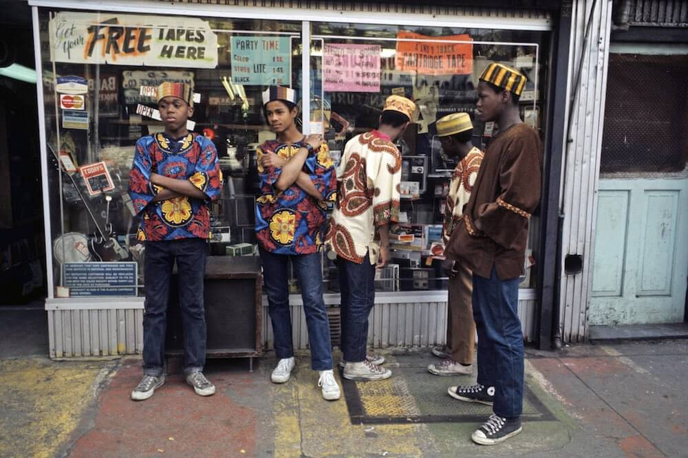 Harlem: The Ghetto. New York City- Harlem- juillet 1970: le ghetto; un groupe de jeunes garÁons, coiffÈs de toques et vÍtus de tuniques multicolores, pose devant une boutique de musique. (Photo by Jack Garofalo/Paris Match via Getty Images)