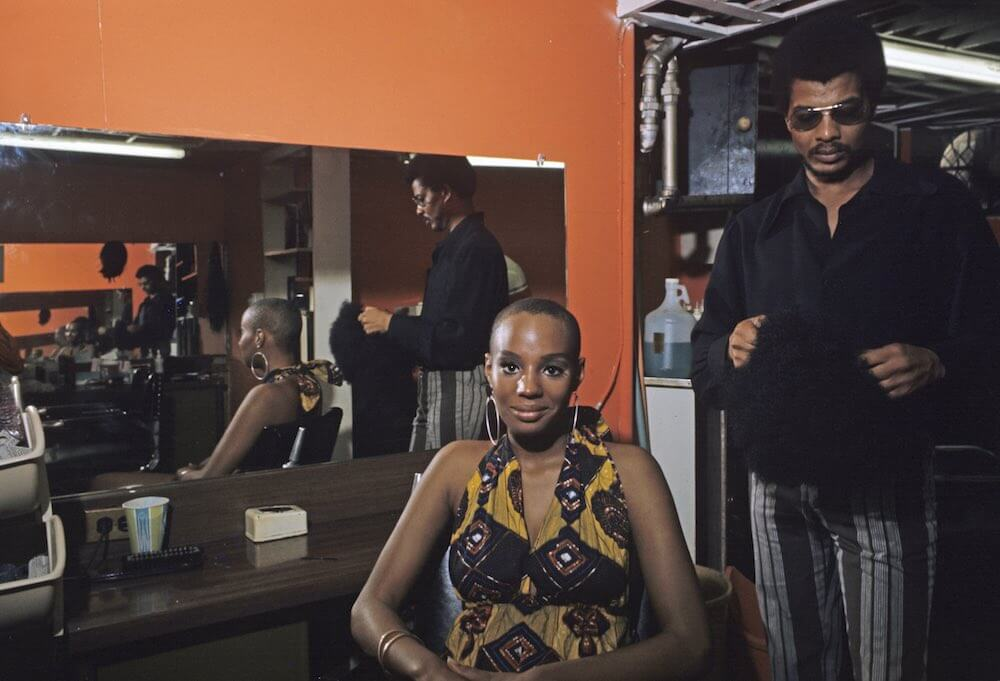 Harlem: The Ghetto. New York City- Harlem- juillet 1970: le ghetto; Chez le coiffeur, une jeune femme afro- amÈricaine sourit, le cr'ne rasÈ. (Photo by Jack Garofalo/Paris Match via Getty Images)