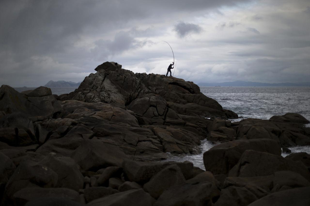 A man casts his fishing rod to the Atlantic sea at the coast of Baiona, Pontevedra province, northern Spain, Sunday, June 9, 2013. (AP Photo/Daniel Ochoa de Olza)