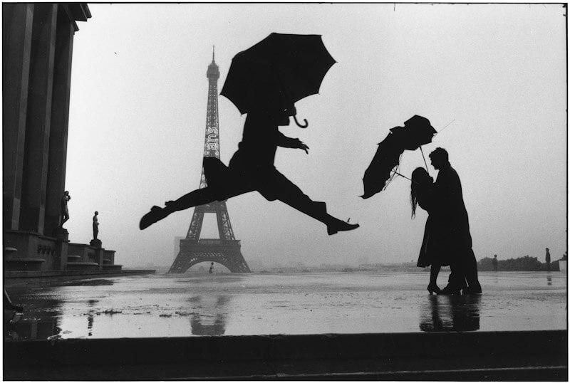 Foto de hombres con paraguas saltando delante de la torre eiffel en parís