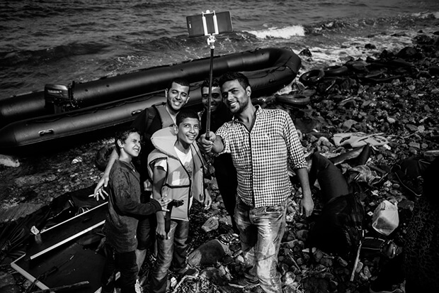 A group of young men posed for a selfie on Eftalou beach after reaching the island.