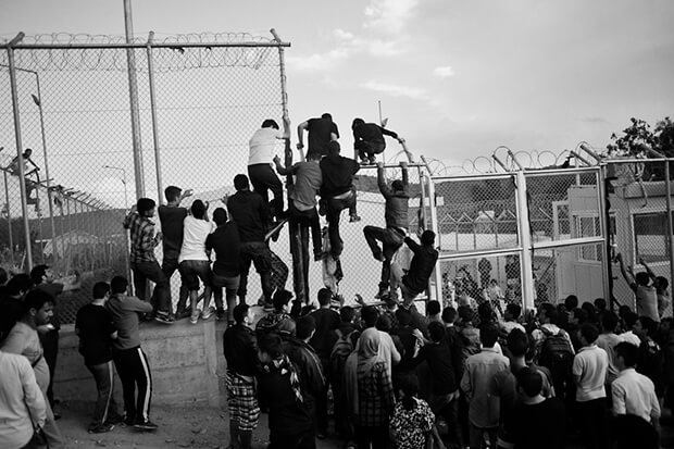 Hundreds of refugees wait for their registration in Moria, Lesbos as the police starts to use teargas because of riots between people from Irak and Afghansitan. Chaotic registration queues leave refugees in future Hot Spot under inhumane conditions for days. Here they start to climb the fences an try to enter the registration point.