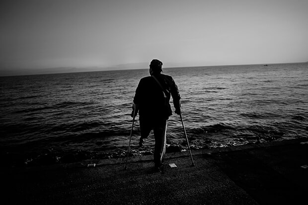 A disabled veteran stands at the beach of Lesbos.