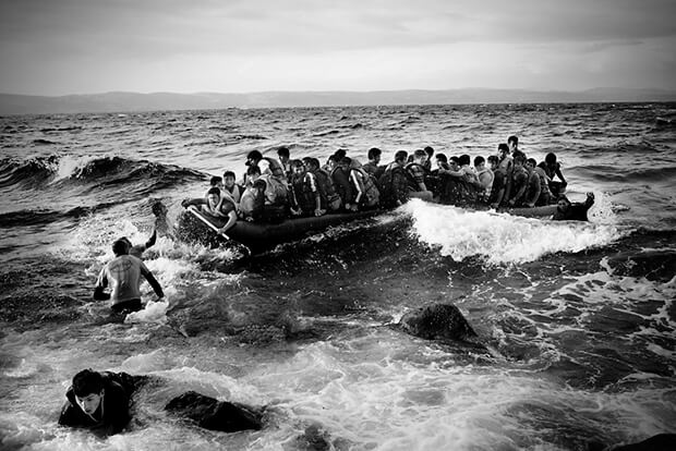 A boat with 45 refugees from Afghanistan reached the north coast of Lesbos. The swell is high and the journey dangerous. Spanish life guards, helping people off the boat.