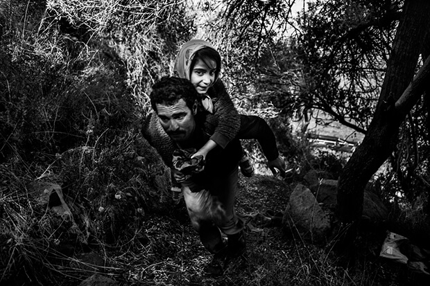 Refugee with his daughter climbs up to a field after arriving from Turkey to Lesbos island, Greece, on a dinghy. They have to walk around 55 kilometers (34 miles) to reach the capital of Lesvos, Mytillini.