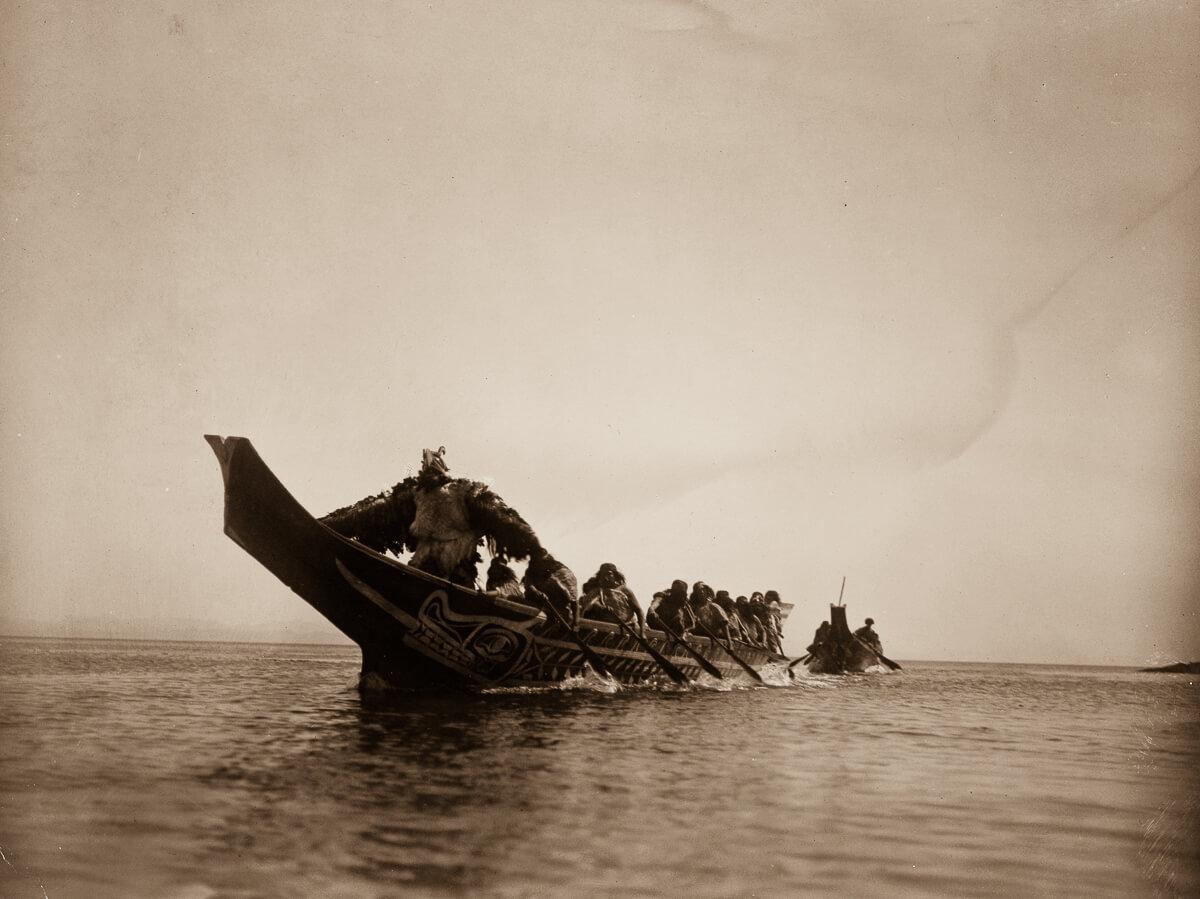Indios nativo americanos en canoa atravesando un río
