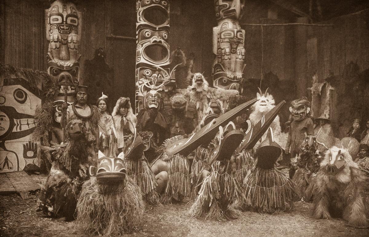 Indios nativos americanos disfrazados junto a un totem