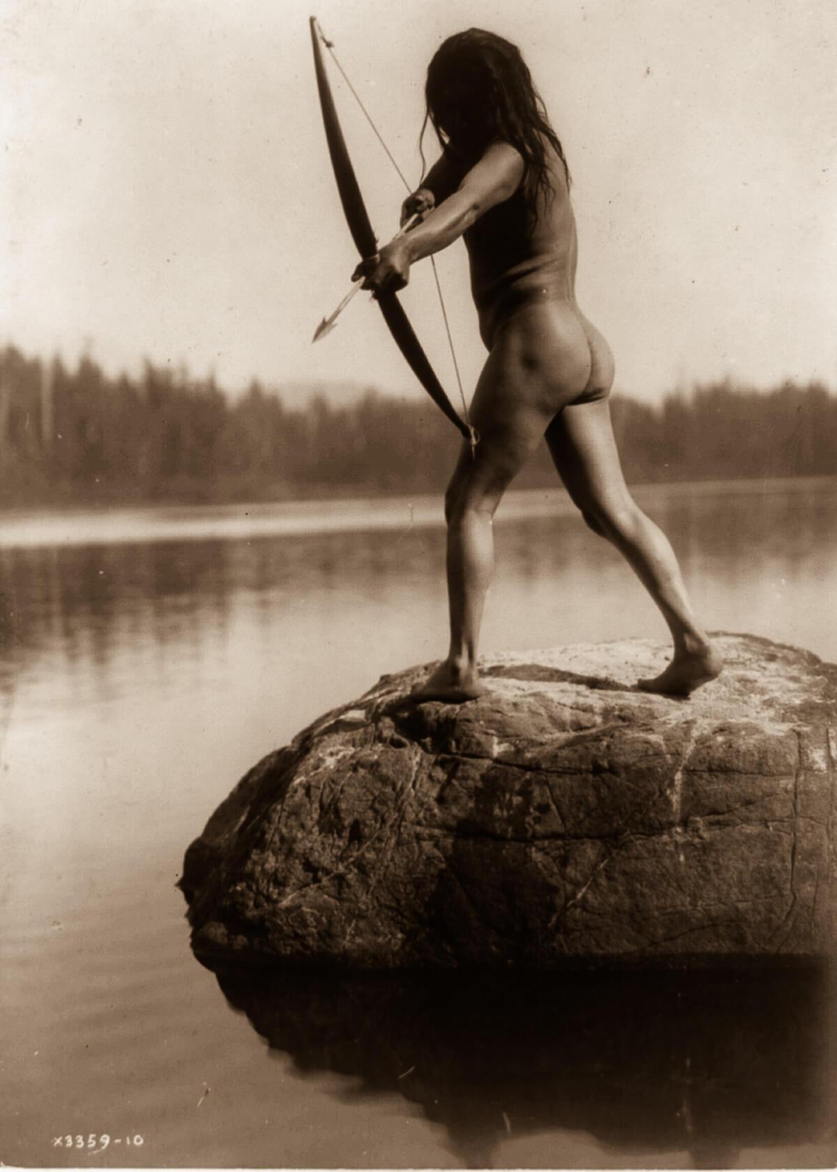 Indio americano cazando con arco en el río