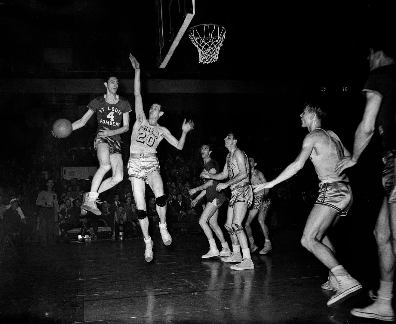 Red Rocha (4), St. Louis Bombers center, goes up in the air to make a pass in Basketball Association of America playoff game with the Philadelphia Warriors at the Arena, March 30, 1948. Chuck Halbert, lanky Warriors center, also leaves the floor in an attempt to block the pass. Others are unidentified. (AP Photo/Warren M. Winterbottom)
