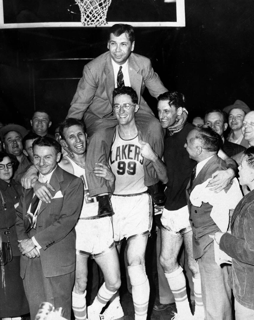 Minneapolis Lakers hoist coach John Kundla and carry him to their dressing room after beating the New York Knickebockers 82-65 April 25, 1952, and winning their fourth National Basketball Association title in five years.Left to right are Max Winter, Laker manager (dark suit); Slater Martin (22); George Mikan (99) ; Jim Pollard ( sweatshirt) and Ben Berger Laker president. (AP Photo)