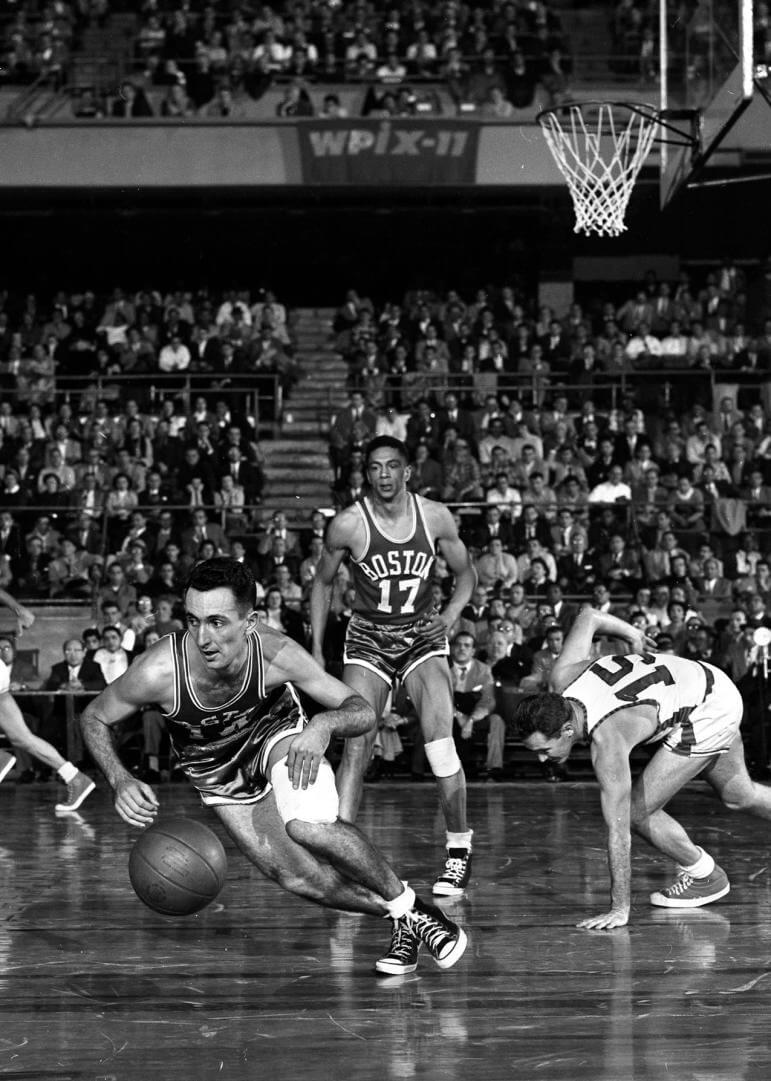 Decked by Cousy. Dick McGuire (right) drops to knee as Boston's Bob Cousy outslicks him during fourth period action at Garden. Alan Barksdale (center) seems awed by teammate Cousy's daring, but things evened up for Knicks as they pulled away to 88-83 victory. (Photo by Charles Hoff/NY Daily News via Getty Images)