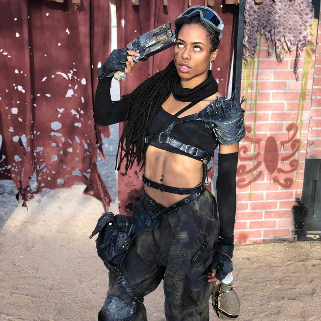 chica disparandose vestida de temática post-apocaliptica