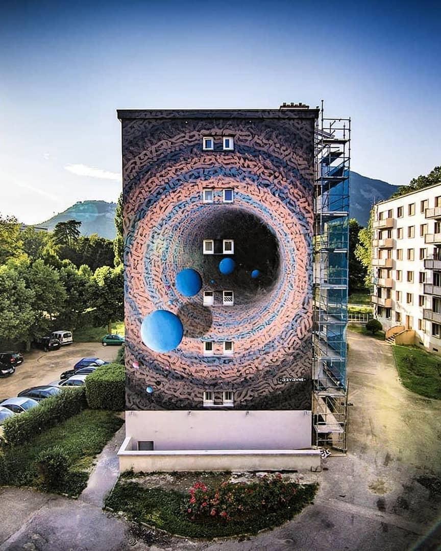 mural gigante con planetas y letras de Izzi-Izvne