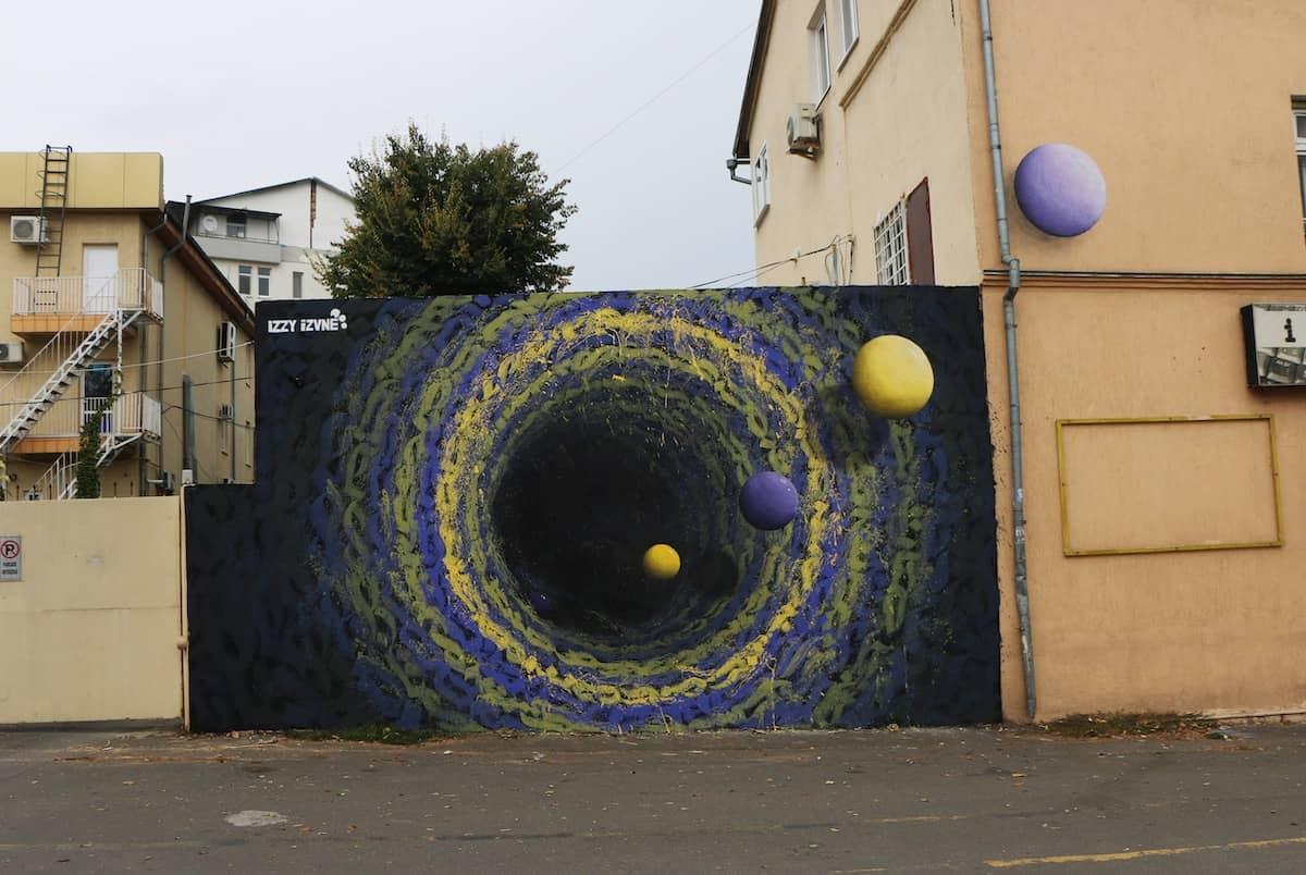 mural colorido de un agujero negro street art de Izzi Izvne