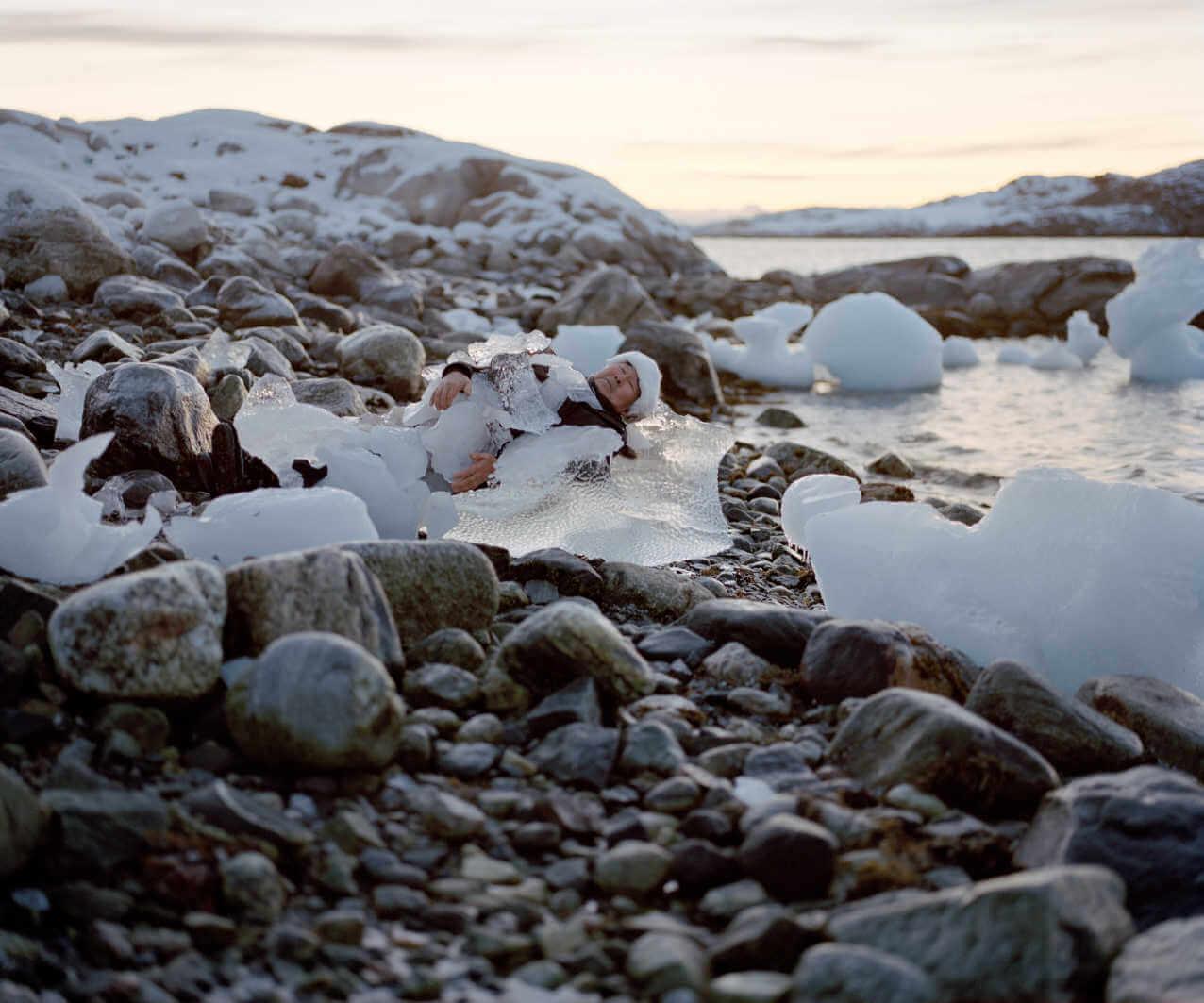 mujer tumbada en el hielo simulando una escultrura humana