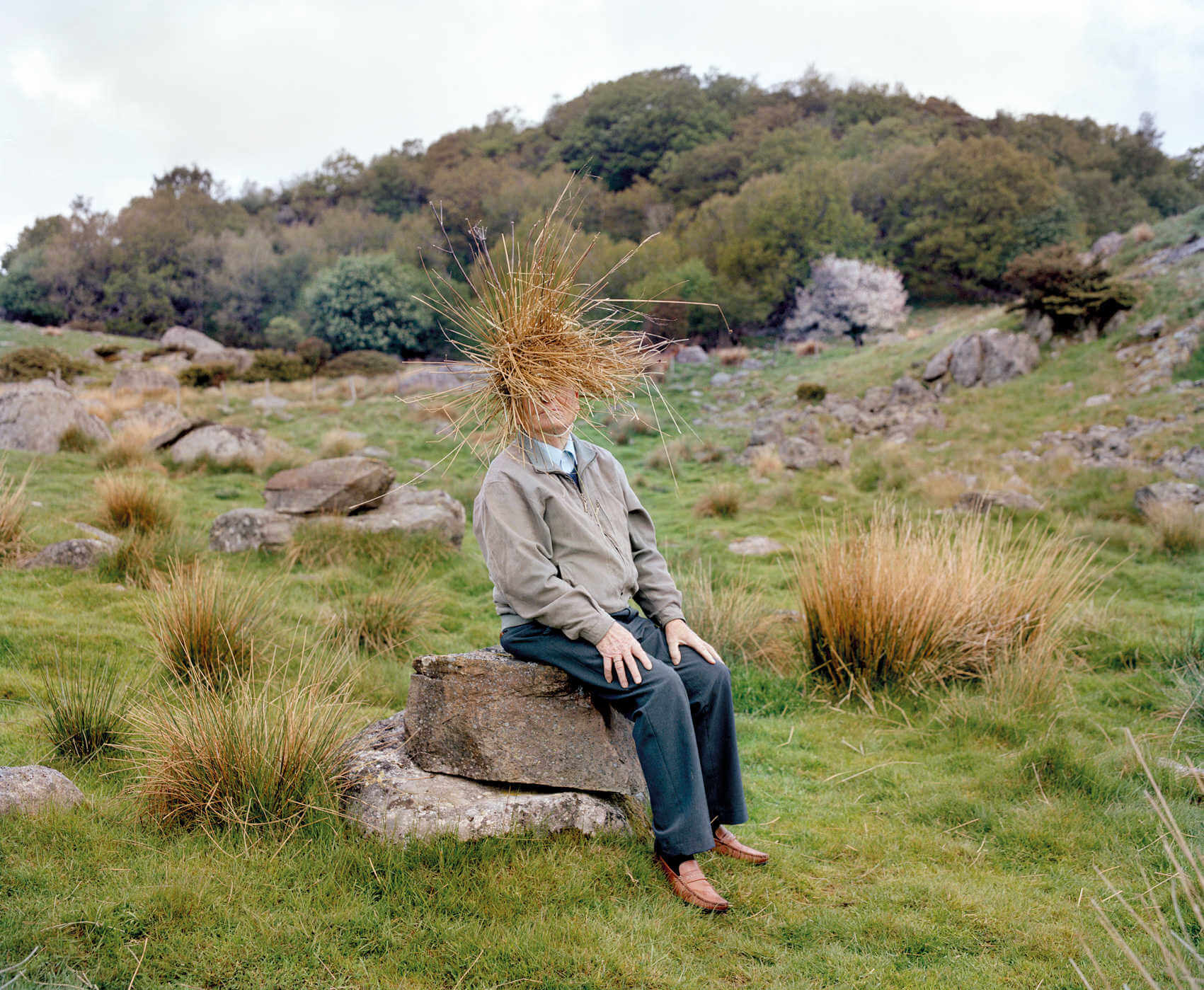 hombre sentado en una roca simulando una escultura humana