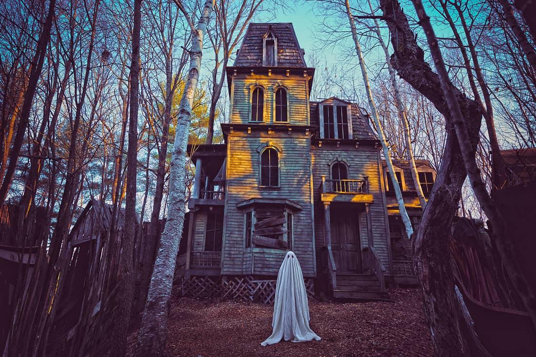 fotografía de un fantasma delante una casa abandonada