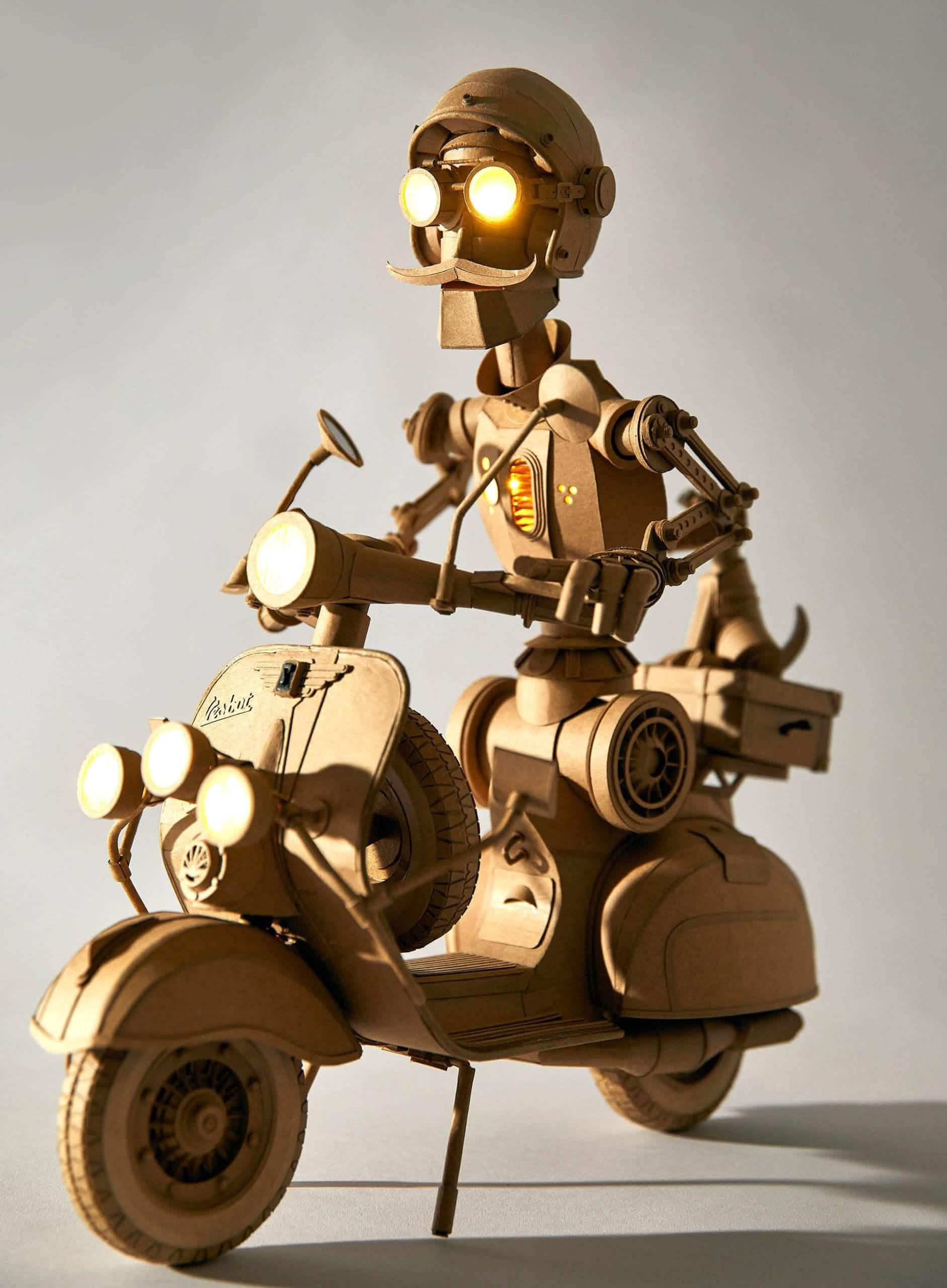 escultura de cartón de un robot en moto