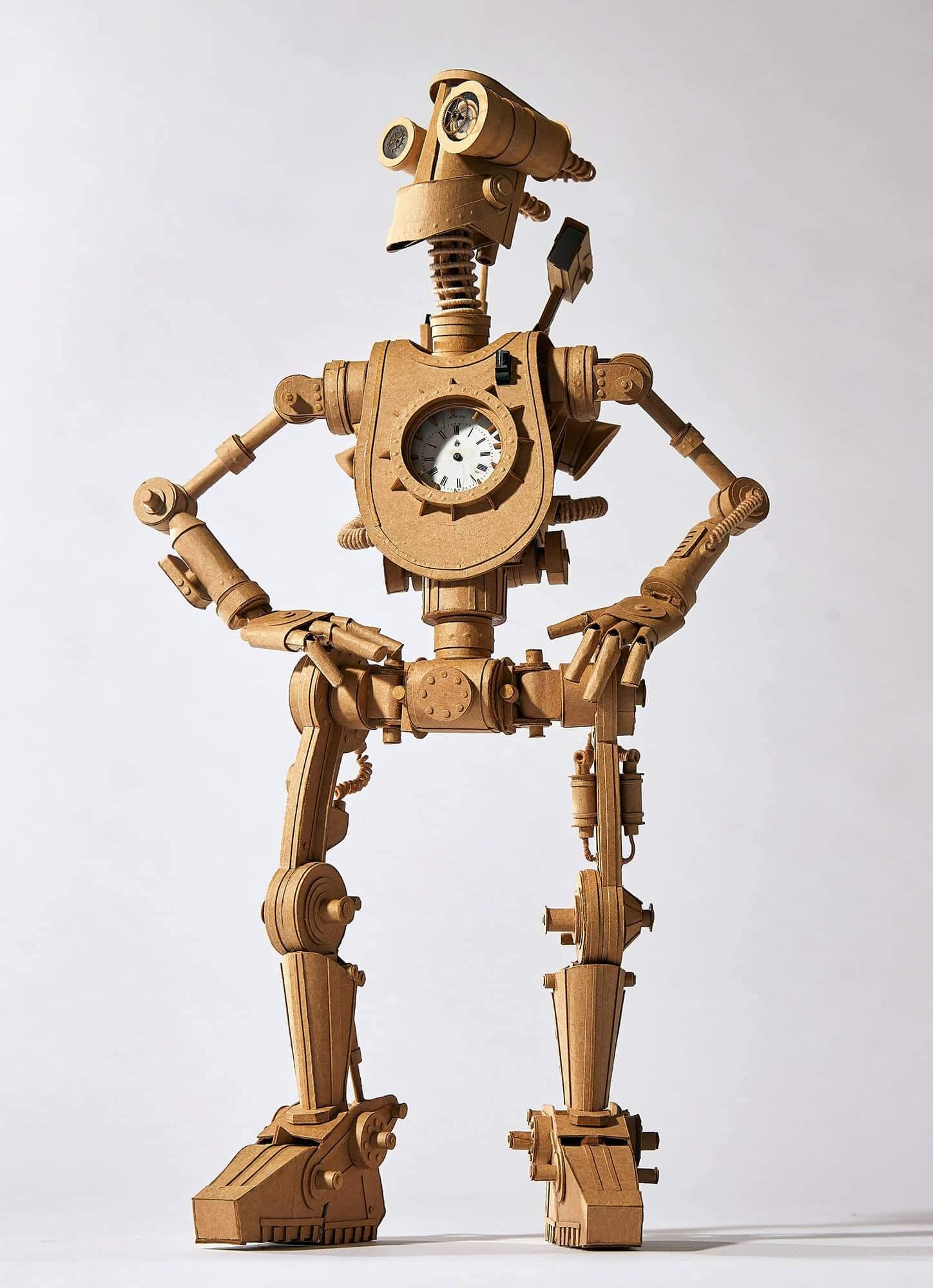 Robot de cartón con un reloj en el centro hecho por greg olijnyk