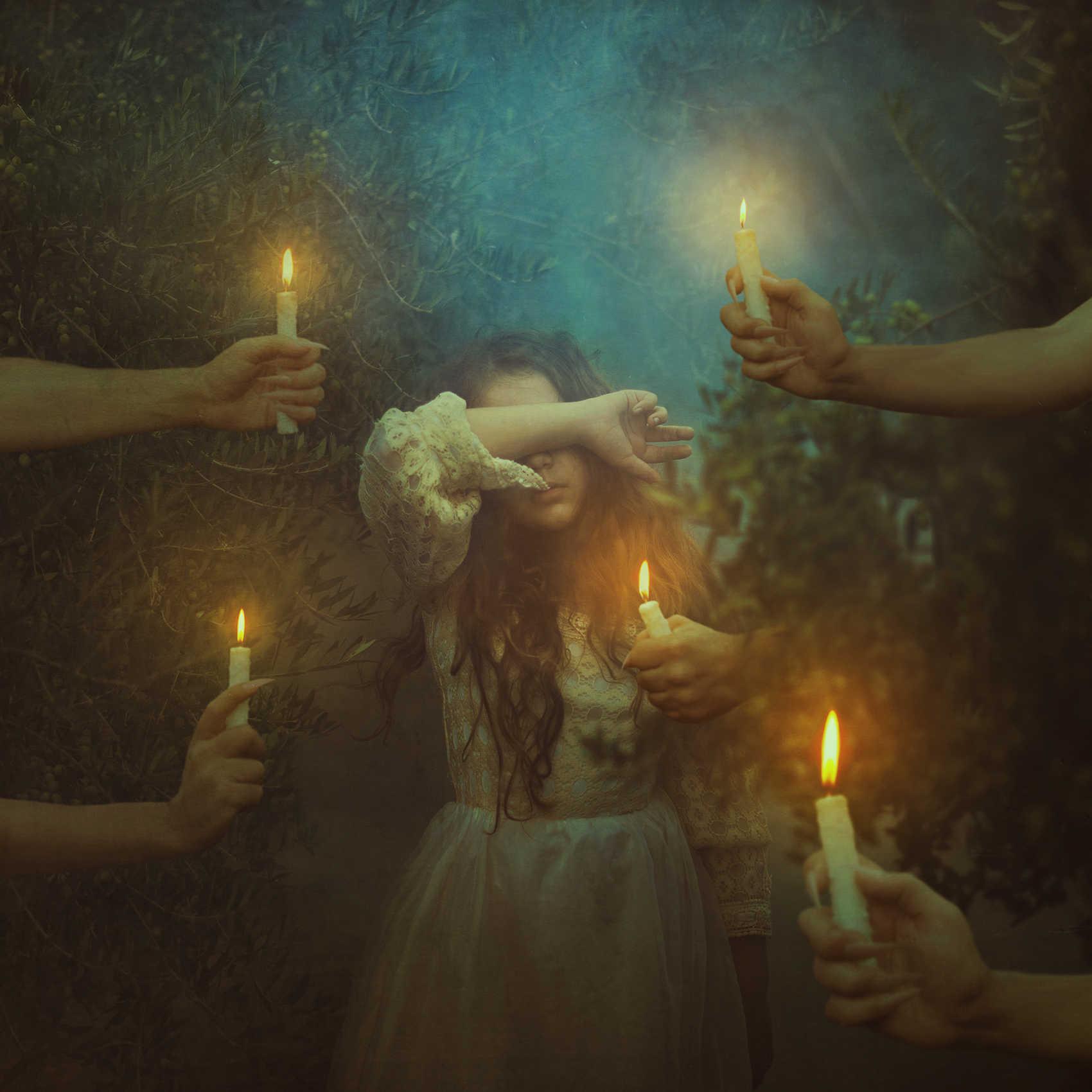Fotografía de una niña con manos llenas de velas encendidas