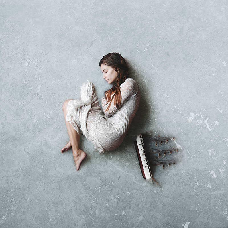 Fotografía de una mujer tumbada en el hielo junto a un barco, hecha por frank diamond