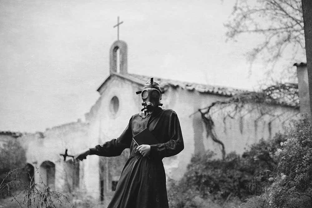 fotografía de mujer con mascara de gas frente una iglesia