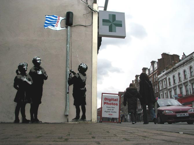 Niños subiendo bolsa bandera de tesco street art de banksy